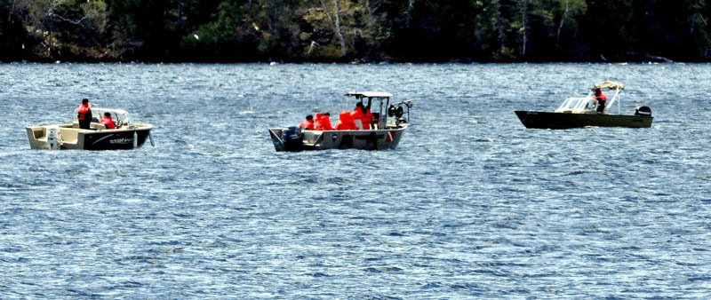 Maine Warden Service boats and personnel drag sonar equipment from the center boat on Tuesday, while doing a grid search of the bottom of Rangeley Lake for the bodies of two snowmobile operators, who went through the ice last Decermber.