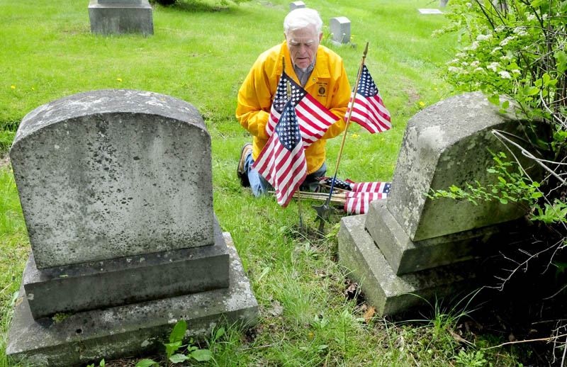 Veteran Burns Hillman places American flags near the grave of a Civil War Medal of Honor recipient buried at the Pine Grove cemetery in Waterville on Thursday. Hillman has decorated graves for close to 50 years.