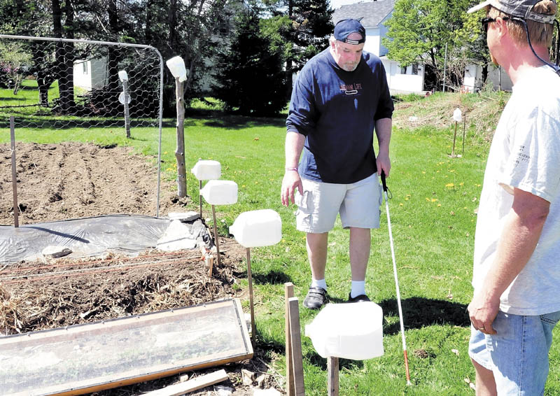 Gardener David Perry, right, watches as Deon Lyons negotiates through a vegetable garden in Fairfield that uses milk jugs and other markers to help visually impaired people work in the garden.