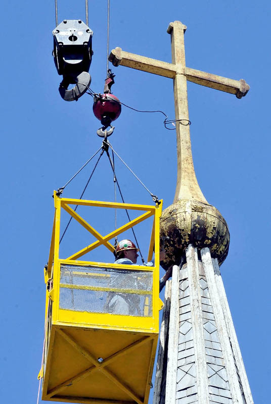 Gene Green works 60 feet above the ground, in a cage suspended from a crane, as he labors to sever the cross from the steeple atop St. Francis de Sales Catholic Church in Waterville on Tuesday.
