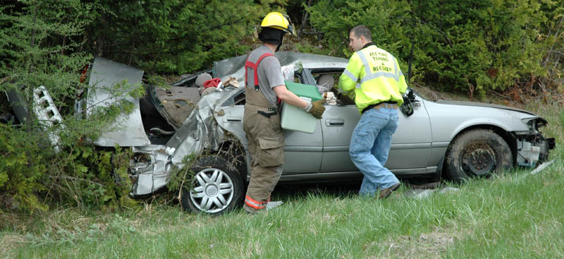 Members of the Pittsfield Fire Department recover items thrown from a 2000 Toyota that crashed and rolled over Thursday afternoon in the northbound lane of Interstate 95 in Pittsfield. Two people from New York were taken to a local hospital, according to state police.
