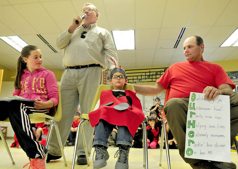 Regional School Unit 18 Transportation Director Lennie Goff, standing, acknowledges students Abby Whitcomb and Michael Remmers and bus driver Nathan Philbrick during an assembly at the James Bean School in Sidney on Tuesday. Whitcomb is credited with alerting Philbrick that Remmers was choking on candy recently allowing Philbrick to use his resuscitation training to assist.