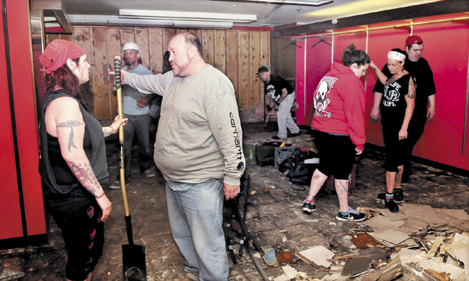 Mike Soracchi, owner of the former Levine's clothing store in Waterville, and INK-4-LIFE tattoo parlor co-owner Mona Juliano speak on Tuesday, as business employees renovate the big, large and tall section of Levine's for the new location of the parlor. Fire destroyed the business last week forcing the move.