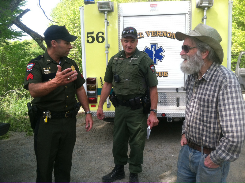 Warden Sgt Terry Hughes, left, and District Warden Dan Christiansen confer with Mark Hedden, 83, moments after he emerged from the woods near his Vienna home on Tuesday.