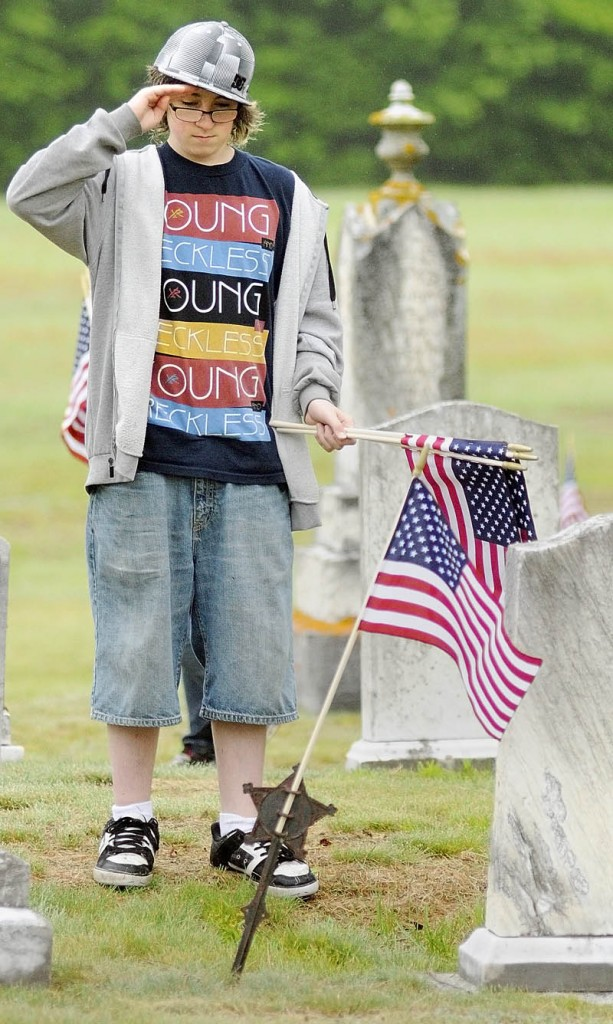 Colby Russell-Leo salutes after placing a flag in a holder in front of the gravestone of a veteran May 25, 2012 at Plains Cemetery in Litchfield.