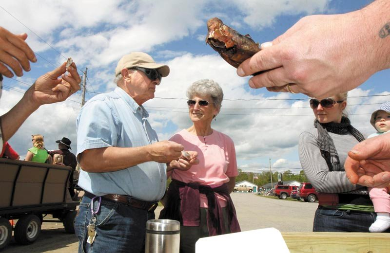 Erma Blakney, of Fairfield, center, looks over as her friend, Edward Fisher, tastes a smoked alewife during the 2nd annual Benton Alewife Festival on Saturday. Rob Hebert, who smoked the fish, said it takes about 12 hours to smoke a small fish and 18 hours to smoke larger ones. Sampling smoked alewives was just one of numerous activities held at the festival, which ended with a floating bonfire on the Sebasticook River Saturday evening.
