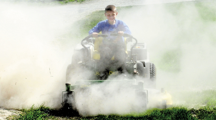 Egide Dostie kicks up a small dust storm while mowing the dry lawn at the family farm in Fairfield on Tuesday. More rain is on the way later this week to reduce fire danger.