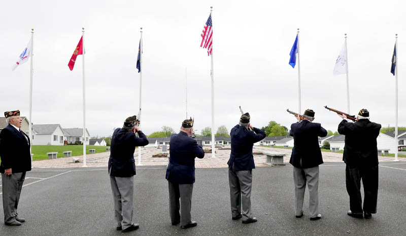 The Winslow VFW 8835 color guard does a 21-gun salute following the raising of a large American flag during a ceremony at the Central Maine Veterans Memorial Park in Winslow on Thursday. The organization donated six armed services flags and two-dozen smaller American flags for flower pots.