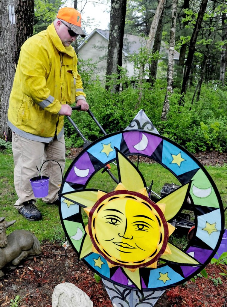 The only sun to be found on a rainy Sunday was an ornament in a garden at Pauline Tuttle's home in Clinton, as her son-in-law, Michael Flanders worked. Several other relatives offered to do outside chores for Tuttle as a Mother's Day gift.