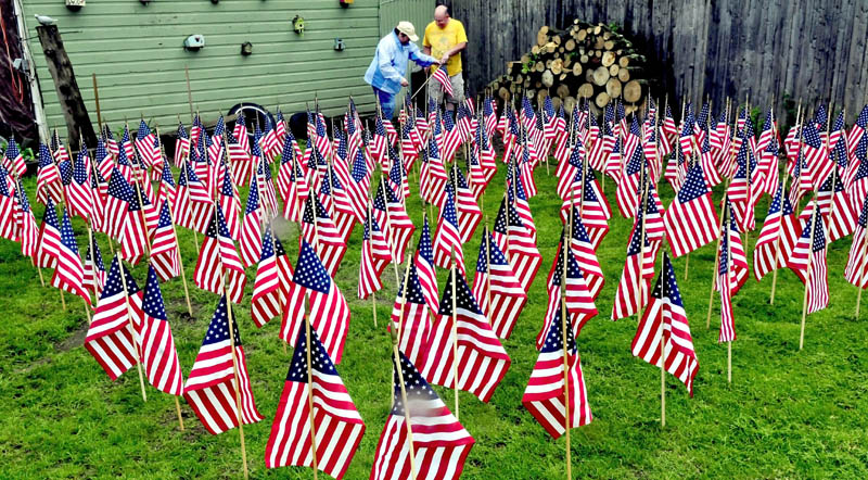 Heather and Ralph Merrow on Sunday set out to dry, at their home in Waterville, some of the 500 American flags that were left over after members of Boy Scout Troop 436 placed them on graves of veterans at the Maine Veterans Cemetery in Augusta recently. The flags will be stored until needed again.