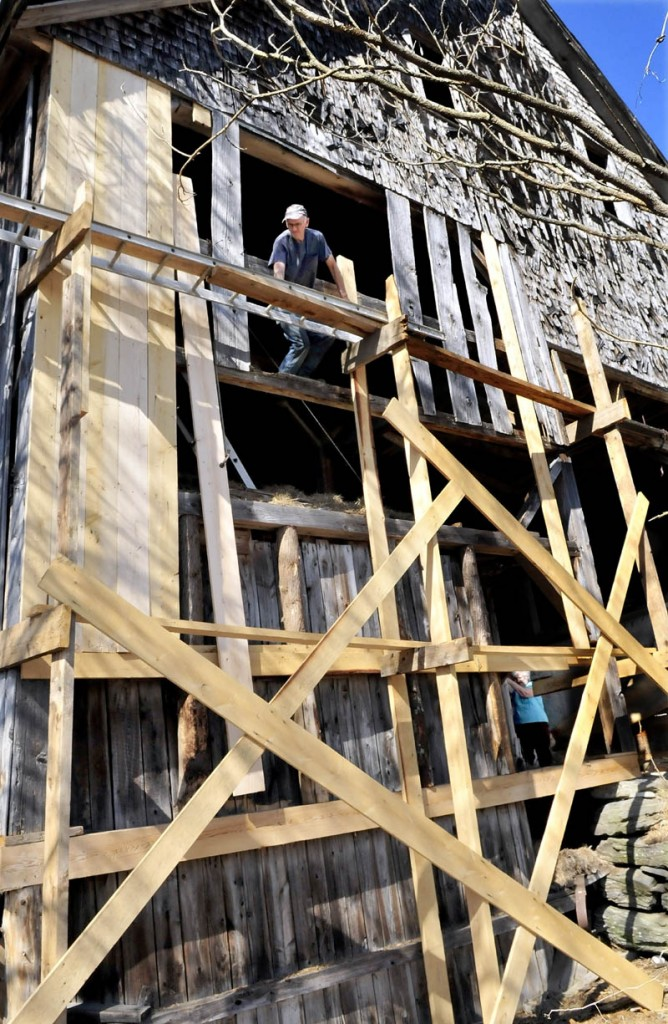 David Frederick lifts a long board into place while repairing his barn in Norridgewock recently. His wife Brenda can be seen at lower right pulling the rope that helped lift the heavy timber.