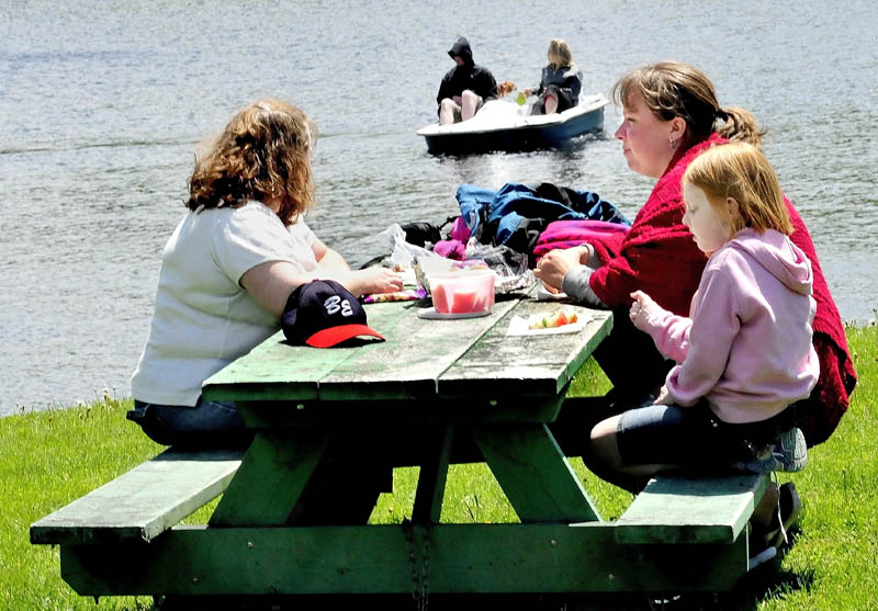 """The sun finally poked out after a week of dreary rain and clouds bringing picnickers and boaters to Messalonskee Lake in Oakland on Monday. Enjoying a lunch outside are, from left, Chrystal Dakin, Kim Corriveau and MaryRuth Dakin. """"It was starting to get depressing,"""" Corriveau said, referring to the damp weather."""