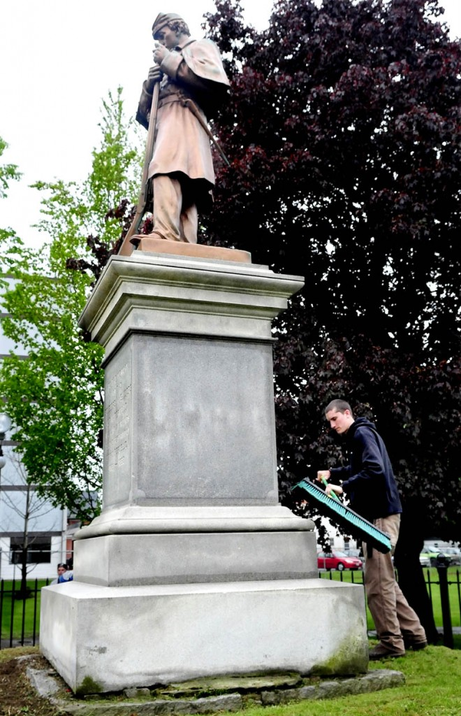 Nate Bernier of the Waterville Parks and Recreation Department brushes grass clippings off the Civil War monument in Veterans Park on Wednesday. The park will be site of Memorial Day events.