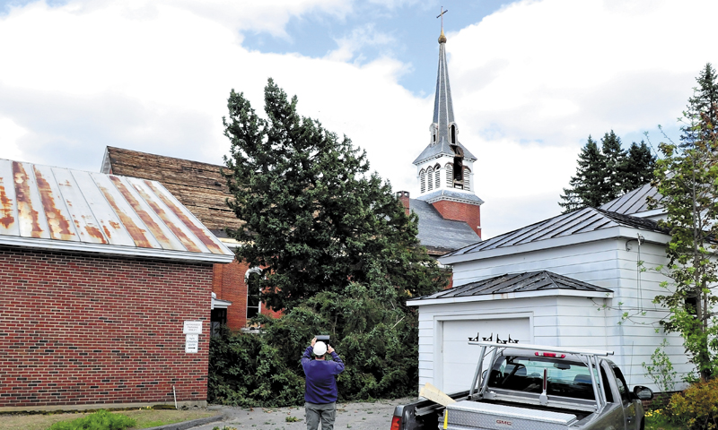 The second of two spruce trees begins to fall beside the St. Francis de Sales Catholic Church in Waterville on Monday. The church will be taken down this summer to make way for a housing project. The parish building, at left, and the building on the right will be torn down later this week.