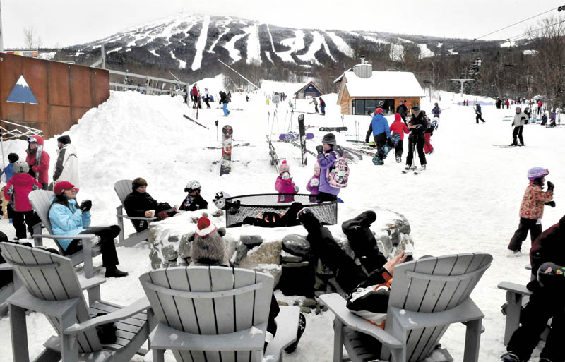 Skiers and snowmobilers relax around an outdoor fire at the base lodge at Sugarloaf.
