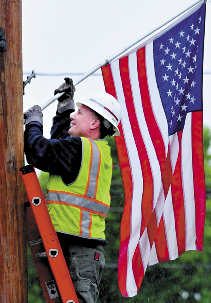 Tom Williams of the Fairfield Public Works department places an American flag in town on a rainy Tuesday.