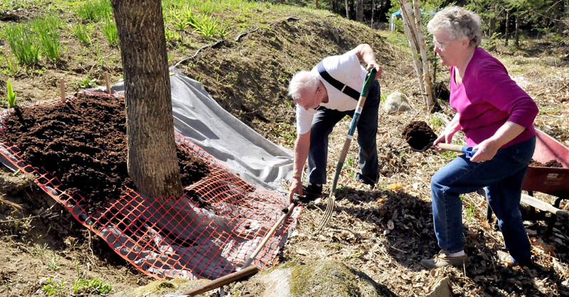 Wilmer and Marlene Redlevske shovel mulch over a tarp to keep weeds from encroaching on a flower garden at their home in Mercer recently.