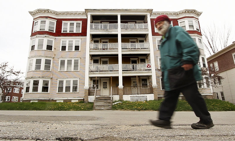 Roland Hamel of Lewiston walks past a condemned multi-unit dwelling on Walnut Street in a city where officials say abandoned buildings often hide in plain sight.