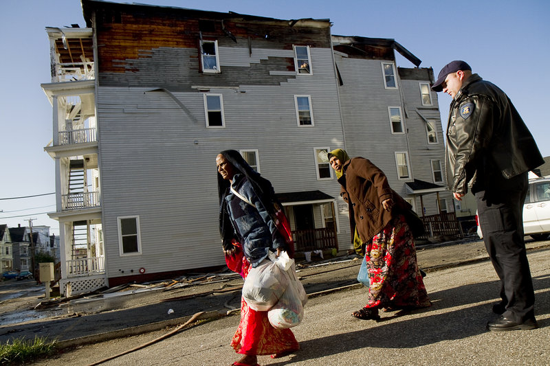 Lewiston police Officer Nick Wiers keeps displaced residents away from the scene of a fire Saturday. Many of the newly homeless people were members of Lewiston's Somali community.