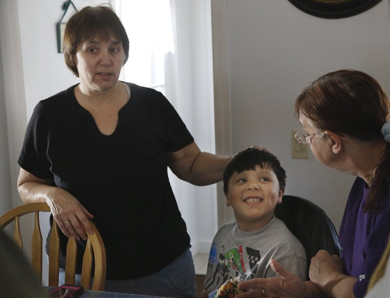 Ja'kai Hayden, 8, smiles while spending time with his grandmother Patricia Gerber, left, and relative Paula Beaulieu during a family gathering in Portland.