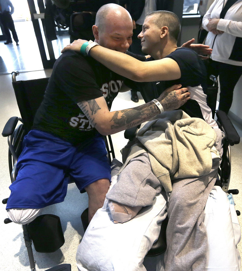 Paul Norden, left, and his brother J.P., right, both suffering limb-loss after the Boston Marathon bombing, embrace after a news conference at Spaulding Rehabilitation Hospital in Boston's Charlestown section Monday, May 13, 2013. (AP Photo/Elise Amendola)