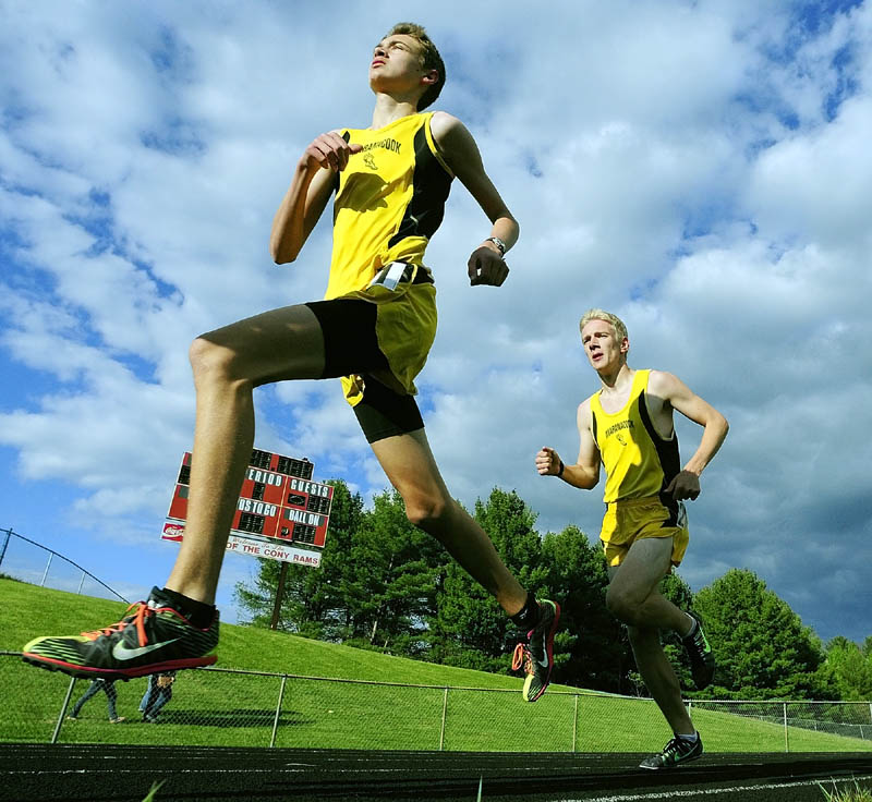 OFF AND RUNNING: Maranacook 1600 meters runners Austin Landry, left, and Jason Stevenson round the bend during the Cony Under the Lights meet on Friday in Augusta.
