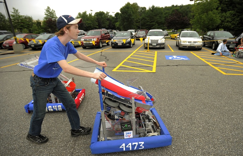 """Colt Seigars, a homeschooler from Augusta, pushes his robot, """"Zaphod,"""" through a parking lot at Fairchild Semiconductor in South Portland Thursday."""