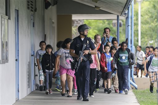 A Santa Monica police officer leads children on a field trip from Citizens of the World Charter School in Los Angeles out of Santa Monica College, where they had gone for a planetarium show, following a shooting in the area, in Santa Monica, Calif., Friday. Two people were found dead Friday in a burned home near the campus, where someone sprayed a street corner with gunfire.