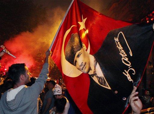 """Turkish protesters, mostly soccer fans of Besiktas who call themselves """"Carsi,"""" wave a poster of Turkey's founder, Kemal Ataturk, as they celebrate in rain at the city's Kugulu Park in Ankara, Turkey, Saturday."""
