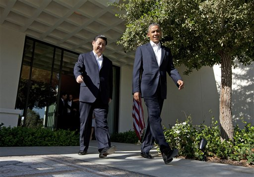 President Barack Obama walks with Chinese President Xi Jinping at the Annenberg Retreat at Sunnylands as they meet for talks Friday in Rancho Mirage, Calif. Seeking a fresh start to a complex relationship, the two leaders are retreating to the sprawling desert estate for two days of talks on high-stakes issues, including cybersecurity and North Korea's nuclear threats.