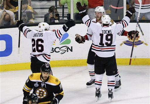 Chicago Blackhawks left wing Bryan Bickell, center, celebrates his goal with Chicago Blackhawks center Jonathan Toews (19) and Chicago Blackhawks center Michal Handzus (26), of Slovakia, during the third period in Game 6 of the NHL hockey Stanley Cup Finals against the Boston Bruins, Monday, June 24, 2013, in Boston. (AP Photo/Charles Krupa) TD Garden