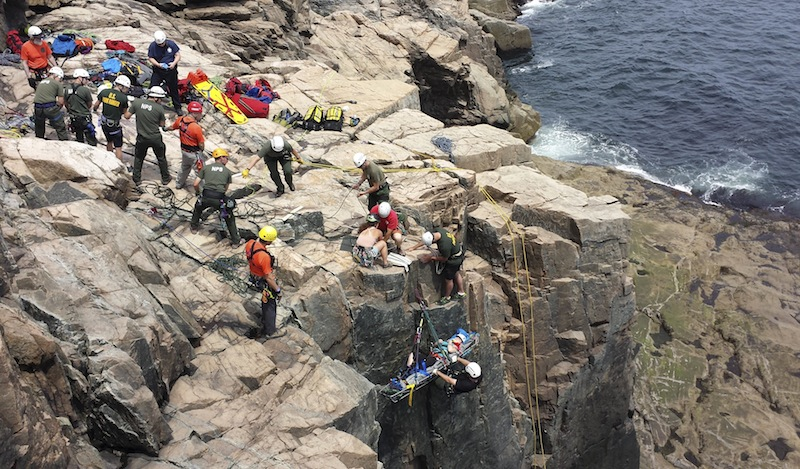 A climber is lifted during a rescue after a climbing accident at the rock face at Otter Cliffs in Acadia National Park in Bar Harbor. Two climbers fell onto a third after a rope broke, park rangers said.