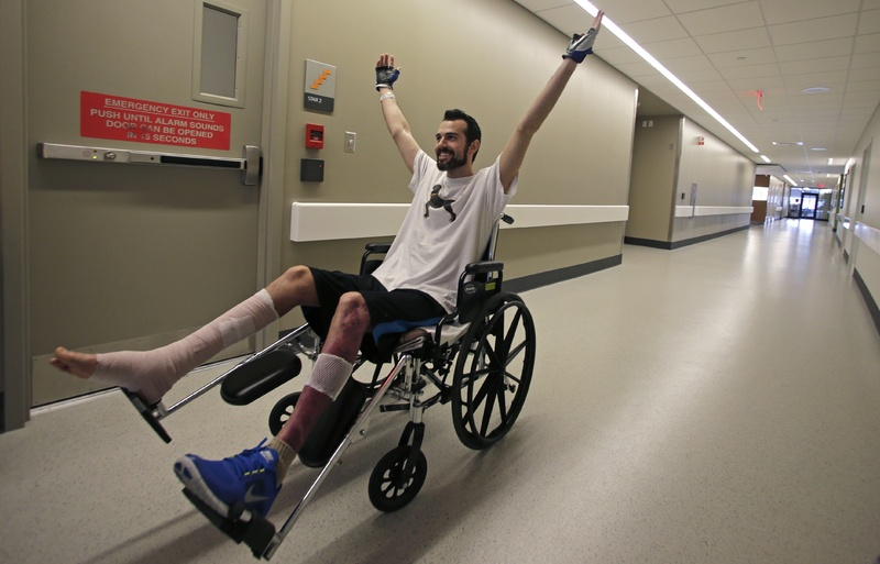 Boston Marathon bombing survivor Pete DiMartino, of Rochester, N.Y., raises his arms after completing a physical therapy session at the Spaulding Rehabilitation Hospital in Boston last month. DiMartino was among those applying for aid through a fund set up for survivors.