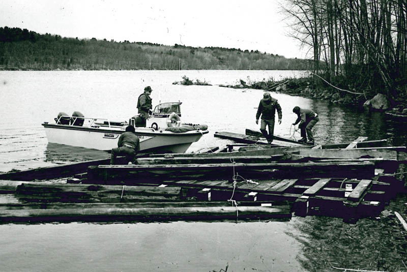 Workers recover timbers of the Fort Halifax blockhouse from the Kennebec River, in the weeks after a 1987 flood destroyed the historic building.