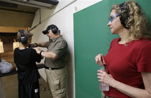 Cheryl Strain, right, watches as instructor Scott Stevens, center, shows her son Rory, 12, how to properly hold a shotgun at a shooting range in Houston on May 19. The Strains live in the first residential area being trained and equipped by a nonprofit that is giving away free shotguns to single women and neighborhoods with high crime rates.