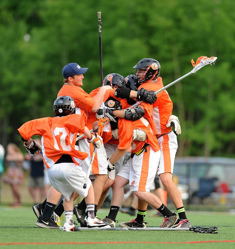 Gardiner Area High School celebrates their 6-5 overtime win over Maranacook/Winthrop High School in the KVAC B boys lacrosse championship game at Thomas College in Waterville.