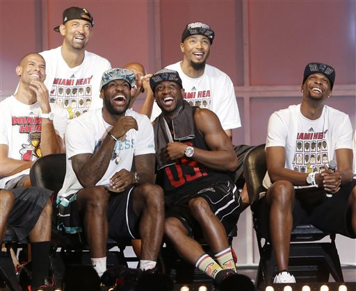 Miami Heat players laugh as they watch highlights of center Chris Bosh, right, Monday, June 24, 2013, during a celebration for season ticket holders at the American Airlines Arena in Miami. Other players from left are: Shane Battier, Juwan Howard, LeBron James, Dwyane Wade and Rashard Lewis. The Heat defeated the San Antonio Spurs 95-88 in Game 7 to win their second straight NBA championship.
