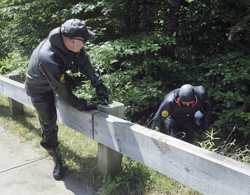 Law enforcement officers wearing wetsuits emerge from bushes during a search for evidence along a road near the home of New England Patriot's tight end Aaron Hernandez on Monday in North Attleborough, Mass.