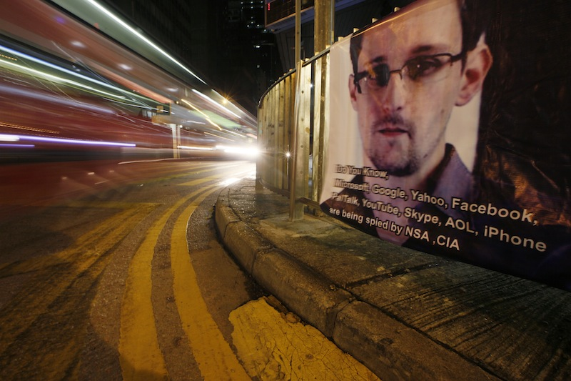 A bus drives past a banner supporting Edward Snowden, a former CIA employee who leaked top-secret documents about sweeping U.S. surveillance programs, at Central, Hong Kong's business district, Tuesday, June 18, 2013. Snowden, the National Security Agency leaker, is defending his disclosure of top-secret U.S. spying programs in an online chat Monday with Britain's Guardian newspaper and attacked U.S. officials for calling him a traitor. (AP Photo/Kin Cheung)
