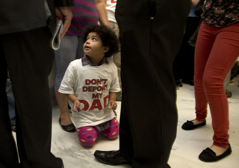 """Jackelin Alfaro, 4, in a T-shirt that reads """"Don't Deport my Dad,"""" sits in the hall with family members outside the House Judiciary Committee hearing on Capitol Hill in Washington on Tuesday."""