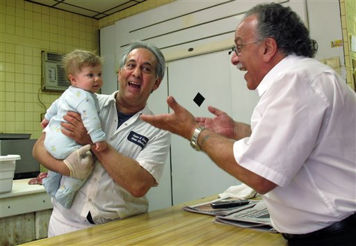 """John Sacco Sr. hands his 6-month-old grandson, Jack Russo, to Pete Canu, a customer in Sacco's Elizabeth, N.J., butcher shop, Thursday. Canu says he liked the realism and human flaws of actor James Gandolfini's Tony Soprano character, but Sacco said, """"The Sopranos perpetuated and spread negative stereotypes about Italian-Americans."""""""