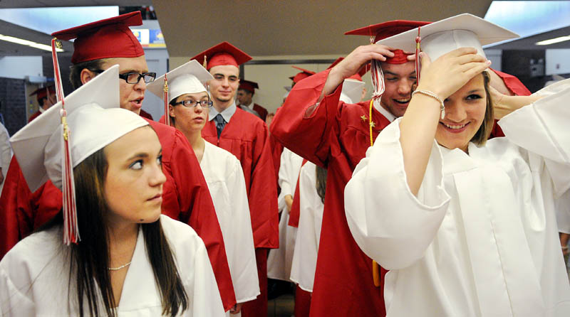 Cony High School seniors hastily adjust their caps while marching into graduation Sunday in Augusta.
