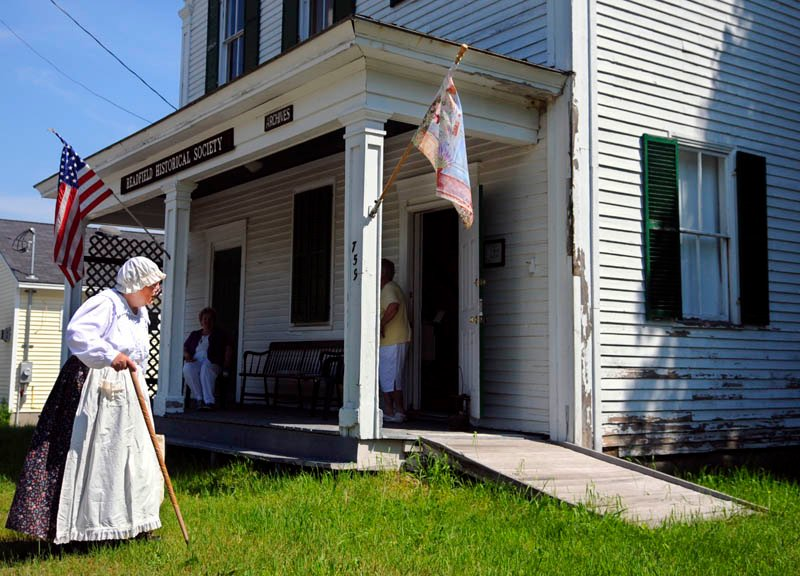 Dale Potter Clark walks in front of the Readfield Historical Society while portraying Releaf Savage Gordon, an early settler of the community, on Sunday, during the society's first open house of the season.
