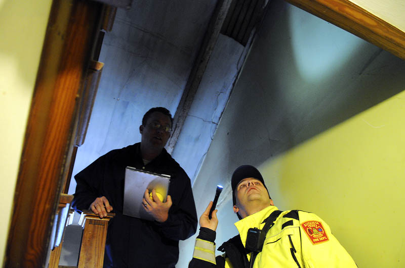 Augusta code enforcement officer Robert Overton, left, and firefighter Arthur True inspect an apartment in the city on Tuesday.