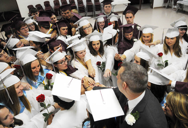 Monmouth Academy seniors surround principal Rick Amero for a group huddle before marching into graduation at the school on Sunday.