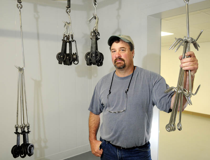 Craig Linke holds onto meat hooks Thursday at Northeast Meats, the new meat processing plant on Brunswick Avenue in Gardiner he is opening. Northeast Meats will prepare Maine animals for consumption.