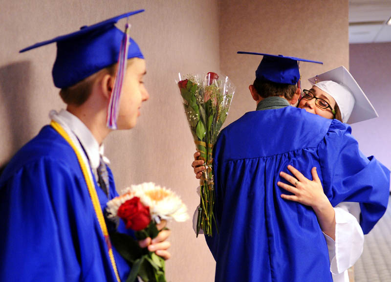 Oak Hill High School seniors Carina Weed, right, hugs Nic Ward while Isaac Fair, left, waits to march during commencement Monday at the Augusta Civic Center.