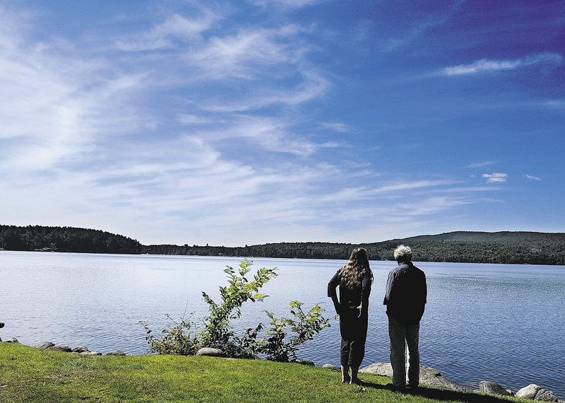 Joanne Moesswild and Paul McKinney, both of Belfast, look out at Long Pond from the picnic area behind Day's Store on a warm sunny Wednesday afternoon in Belgrade Lakes.