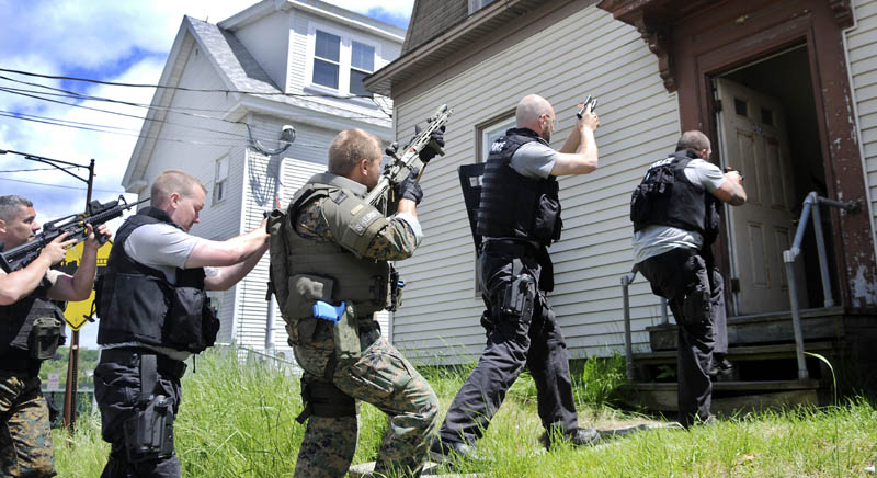 Police officers from across New England enter a building on Water Street in Augusta on Tuesday during the basic Special Weapons and Tactics training school being taught this week by the National Tactical Officers Association. The annual program is being attended by 13 police officers from across New England, according to Augusta Police Chief Robert Gregoire, to learn about advanced safety and apprehension techniques. This is third time the class, taught by retired Tulsa, Okla, police officer Bill Yelton, has been sponsored by the city of Augusta, Gregoire said.