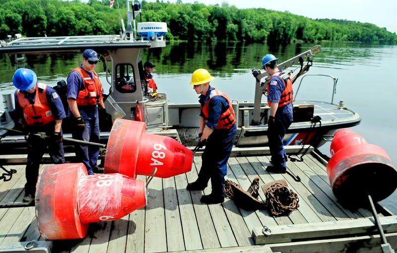 U.S. Coast Guardsmen unload buoys Thursday at the Hallowell boat landing on the Kennebec River. The crew from the Coast Guard's Aids to Navigation station in Portland reset multiple buoys that were displaced by recent high water in the river.